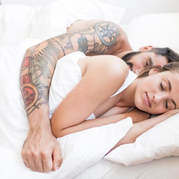Giovane coppia sdraiata sul letto Foto Gratuite