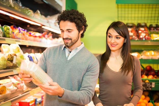 Giovane coppia shopping in un supermercato Foto Premium