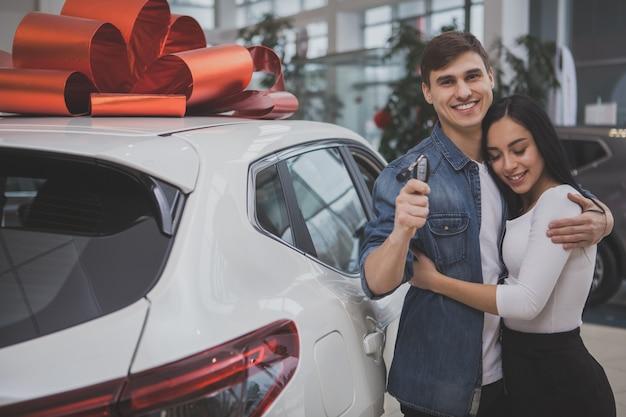 Giovane coppia sposata adorabile che compra insieme nuova automobile Foto Premium