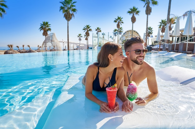 Giovane coppia sulla piscina a sfioro con cocktail Foto Premium
