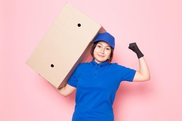 Giovane corriere in polo blu jeans blu con cappuccio in possesso di pacchetto sul rosa Foto Gratuite