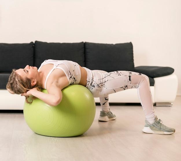 Giovane donna a casa lavorando su palla fitness Foto Gratuite