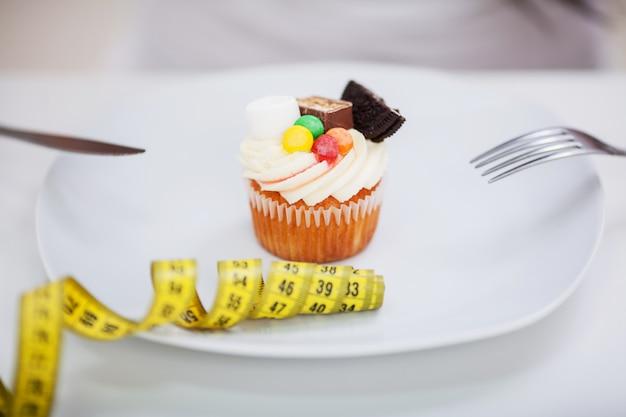 Giovane donna a dieta seduta davanti al piatto con deliziose torte crostate alla crema, guardando il cibo proibito con espressione infelice e affamata, studio Foto Premium