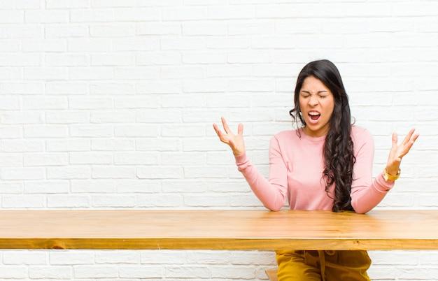 Giovane donna abbastanza latina che urla furiosamente sentendosi stressata e infastidita con le mani in alto dicendo perché io Foto Premium