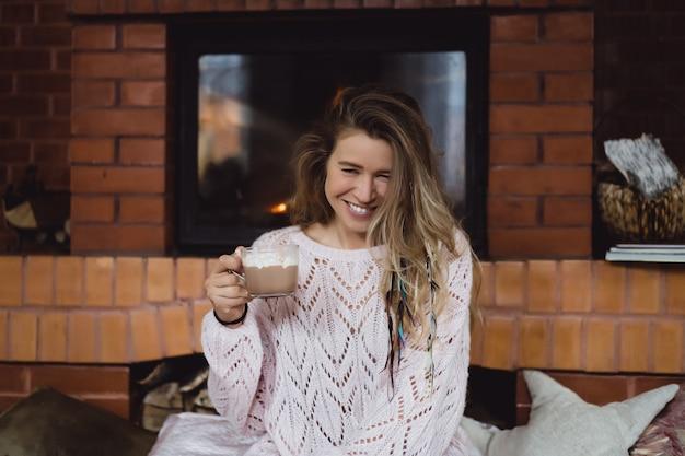 Giovane donna accanto al camino bevi cacao con marshmello con cane. Foto Gratuite