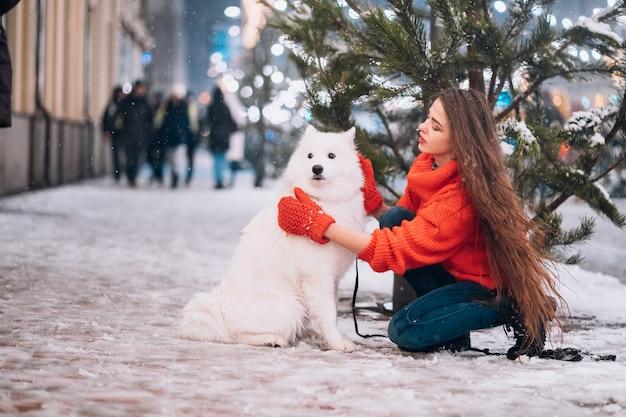 Giovane donna accovacciata accanto a un cane su una strada d'inverno Foto Gratuite