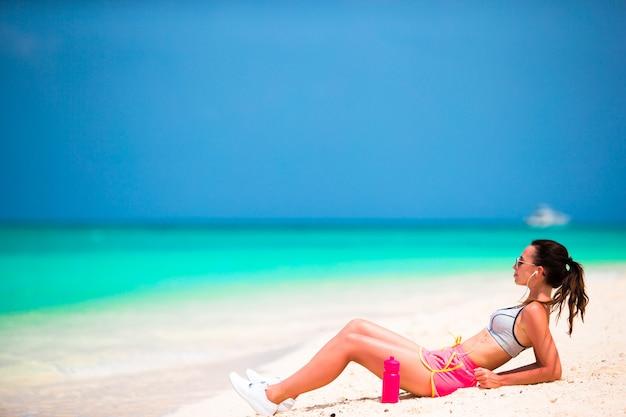 Giovane donna adatta di sport sulla spiaggia bianca tropicale Foto Premium