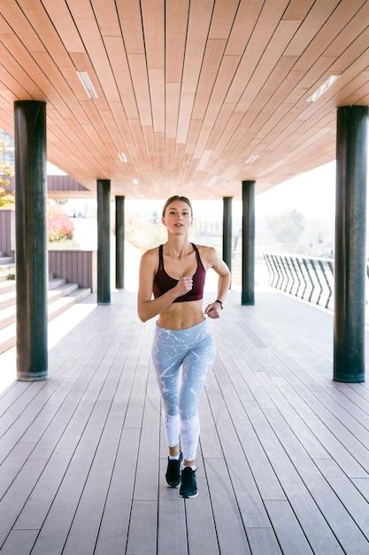 Giovane donna adatta e in buona salute che funziona all'esterno Foto Gratuite