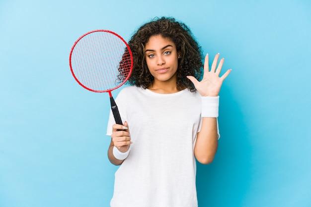 Giovane donna afro-americana che gioca a badminton sorridente allegro mostrando numero cinque con le dita. Foto Premium