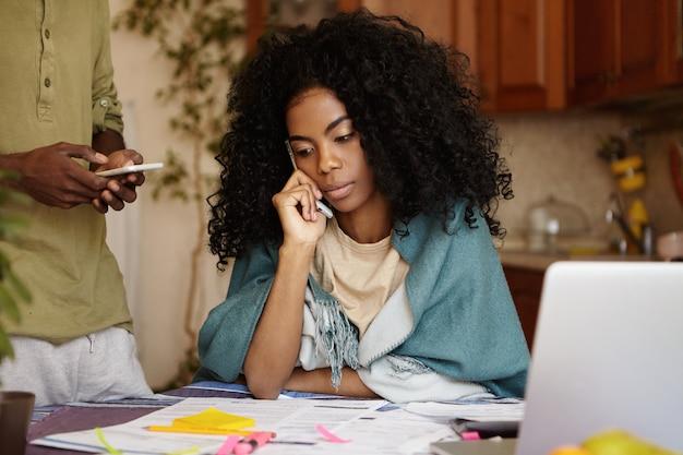 Giovane donna afro-americana con i capelli ricci che sembra preoccupata mentre si lavora attraverso le finanze in cucina, seduto al tavolo con laptop e documenti, parlando al telefono cellulare con la banca informando sul debito di prestito Foto Gratuite