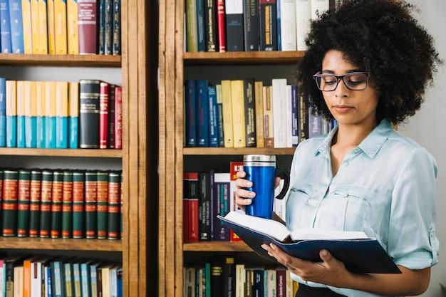 Giovane donna afro-americana con thermos e libro Foto Gratuite