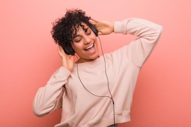 Giovane donna afro-americana con una voglia che balla e ascolta la musica con una cuffia Foto Premium