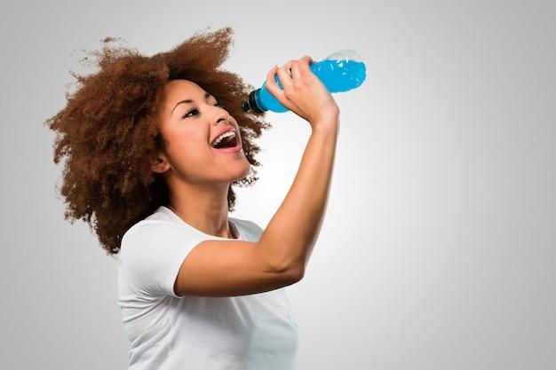 Giovane donna afro fitness bere una bevanda energetica Foto Premium