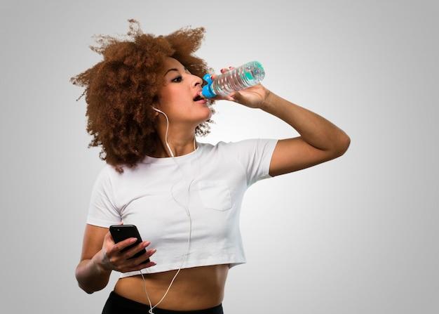 Giovane donna afro fitness in possesso di un mobile e acqua potabile allo stesso tempo Foto Premium