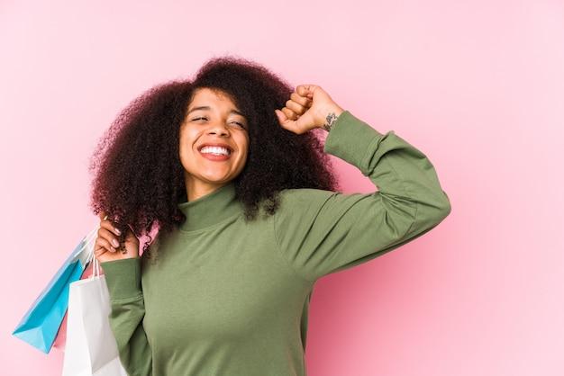 Giovane donna afro shopping giovane donna afro acquisto isolayoung donna afro in possesso di un pugno di rose isolato alzando il pugno dopo una vittoria, concetto vincitore. <mixto> Foto Premium