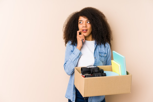 Giovane donna afro trasferirsi a casa isolato giovane donna afro rilassata pensando a qualcosa guardando uno spazio di copia. Foto Premium