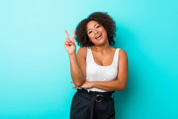 Giovane donna afroamericana allegra e spensierata che mostra un simbolo di pace con le dita. Foto Premium