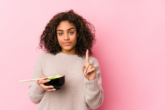 Giovane donna afroamericana che mangia le tagliatelle che mostrano numero uno con il dito. Foto Premium