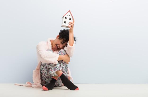 Giovane donna afroamericana che si siede tenendo un'icona della casa Foto Premium