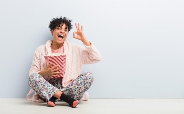 Giovane donna afroamericana che tiene un secchio del popcorn allegro e sicuro che mostra gesto giusto. Foto Premium