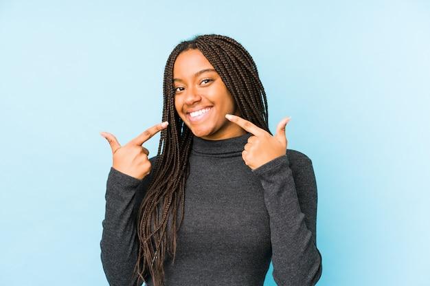 Giovane donna afroamericana isolata sui sorrisi blu della parete, indicante le dita alla bocca. Foto Premium