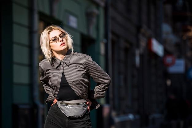 Giovane donna alla moda bionda con la mano sulle anche che distolgono lo sguardo Foto Gratuite