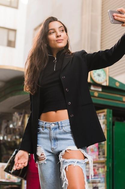 Giovane donna alla moda che prende selfie sullo smart phone all'aperto Foto Gratuite