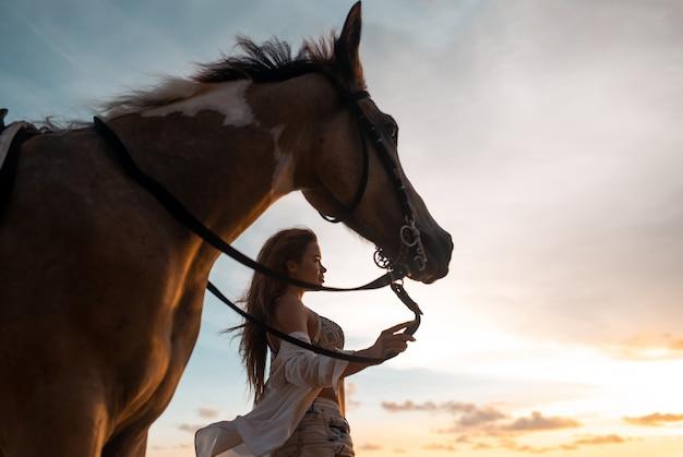 Giovane donna alla moda felice che posa con un cavallo sulla spiaggia Foto Premium