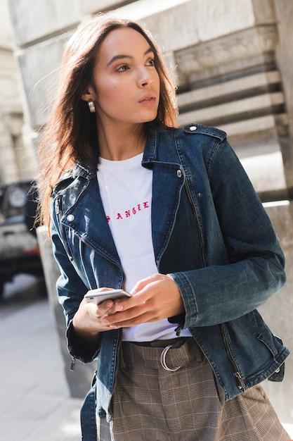 Giovane donna alla moda in giacca di jeans utilizzando smartphone Foto Gratuite