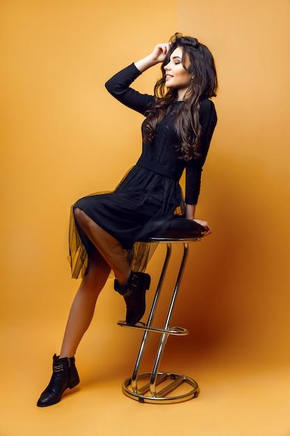 Giovane donna alla moda sulla sedia Foto Premium