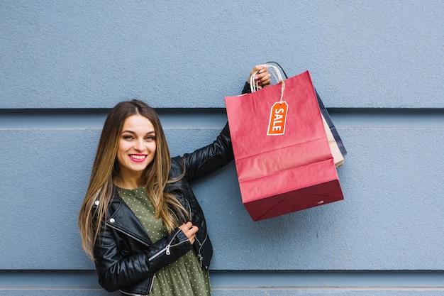 Giovane donna allegra che sta davanti alla parete che tiene molti sacchetti della spesa variopinti Foto Gratuite