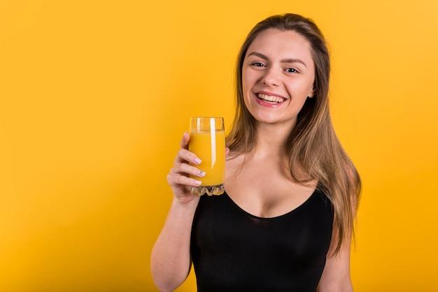 Giovane donna allegra con un bicchiere di succo Foto Gratuite