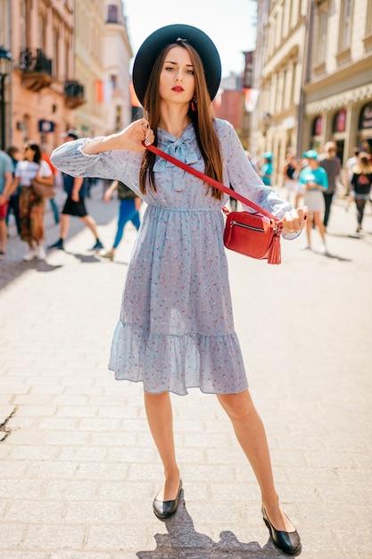 Giovane donna allegra del brunette in vestito elegante e cappello che propongono sulla via della città con la gente Foto Premium