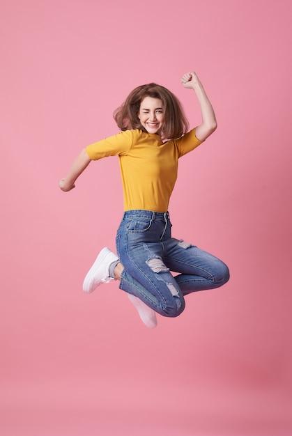 Giovane donna allegra in camicia gialla che salta e che celebra Foto Premium