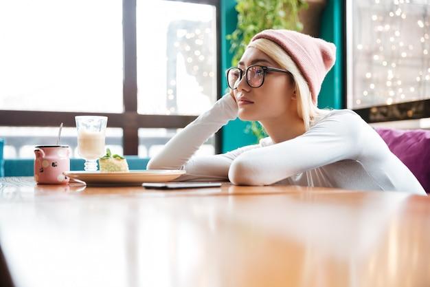 Giovane donna annoiata triste che si siede al tavolo in caffè Foto Gratuite