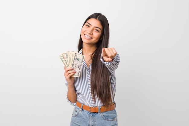 Giovane donna araba che tiene i sorrisi allegri dei dollari che indicano la parte anteriore. Foto Premium