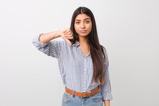 Giovane donna araba graziosa che mostra un gesto di antipatia, pollici giù. disaccordo . Foto Premium