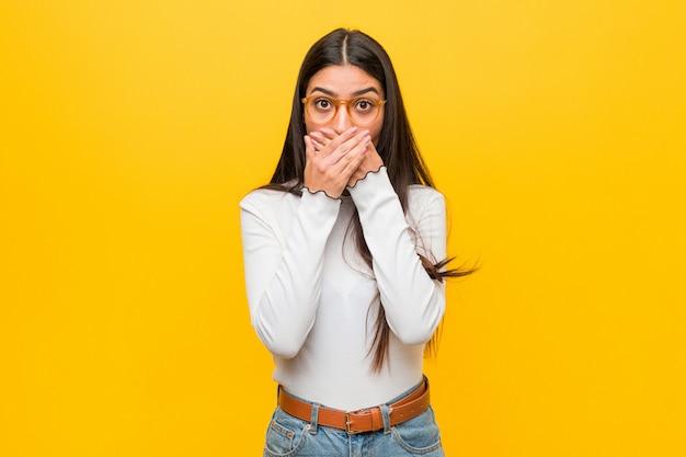 Giovane donna araba graziosa contro la bocca della copertura colpita giallo con le mani. Foto Premium