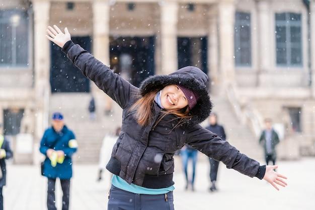 Giovane donna asiatica che gioca la neve quando la neve appena è caduto, viaggia ed ha eccitato il concetto Foto Premium