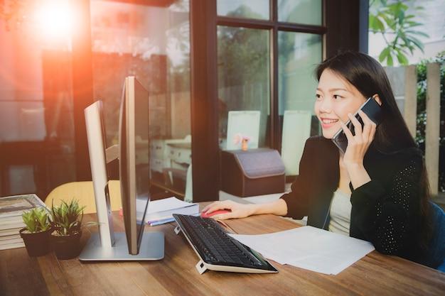 Giovane donna asiatica che intraprende il cellulare e che computa nell'ufficio funzionante Foto Premium