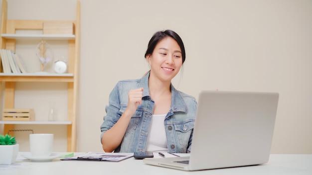 Giovane donna asiatica che lavora facendo uso del computer portatile sullo scrittorio in salone a casa. celebrazione di successo della donna di affari dell'asia che ritiene l'ufficio felice di dancing a casa. Foto Gratuite