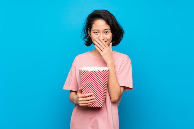 Giovane donna asiatica che mangia i popcorn con espressione facciale di sorpresa Foto Premium