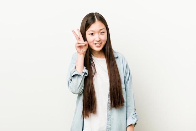 Giovane donna asiatica che mostra il segno di vittoria e che sorride ampiamente. Foto Premium