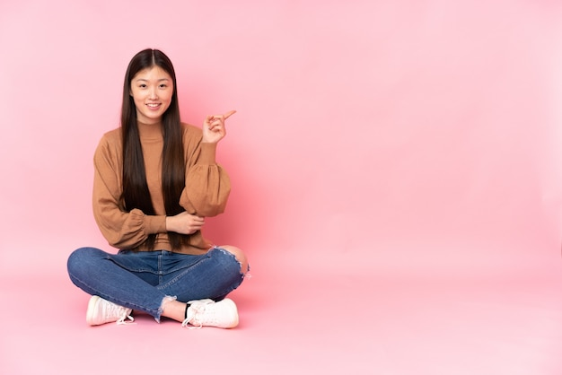 Giovane donna asiatica che si siede sul pavimento sulla parete rosa che indica dito il lato Foto Premium