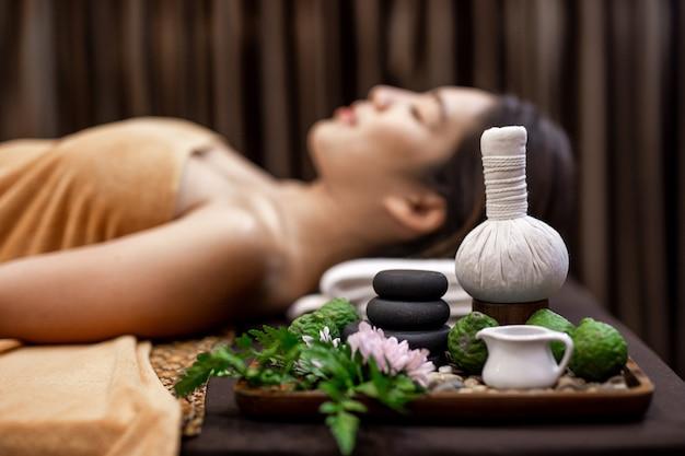 Giovane donna asiatica che si trova sul letto nel massaggio della stazione termale. Foto Premium