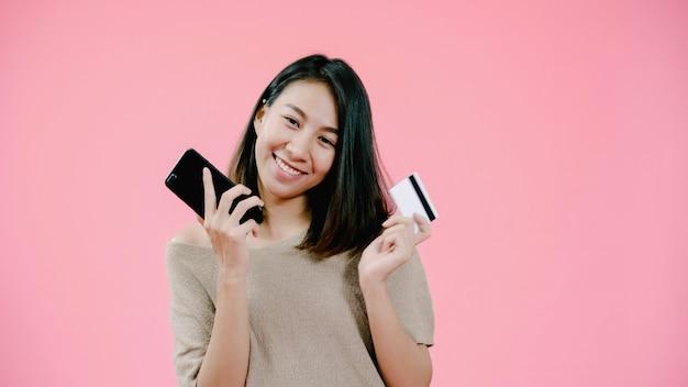 Giovane donna asiatica che utilizza smartphone che compra acquisto online dalla carta di credito che ritiene sorridere felice in abbigliamento casuale sopra il colpo rosa dello studio del fondo. Foto Gratuite