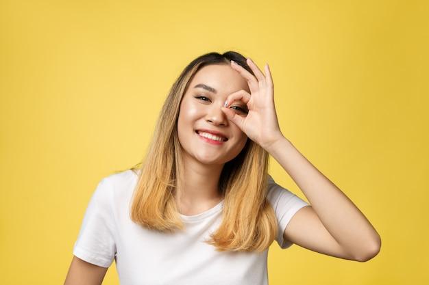 Giovane donna asiatica con l'isolato di gesto del segno giusto sopra fondo giallo. Foto Premium