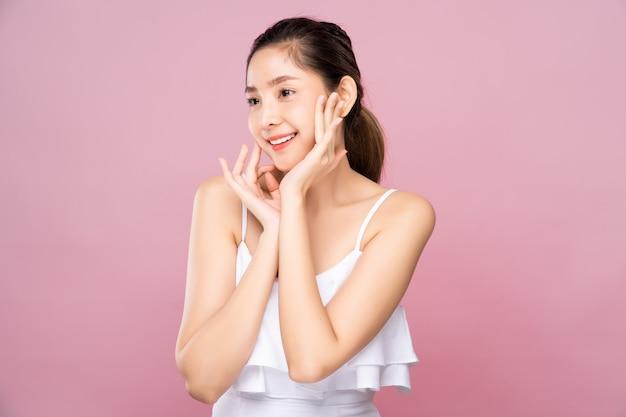 Giovane donna asiatica con pelle bianca fresca pulita che tocca delicatamente il proprio viso nella posa di bellezza Foto Premium