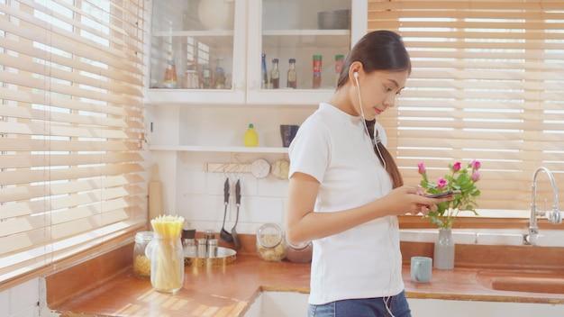 Giovane donna asiatica dell'adolescente che beve caffè caldo facendo uso di musica d'ascolto dello smartphone e controllando sociale Foto Gratuite