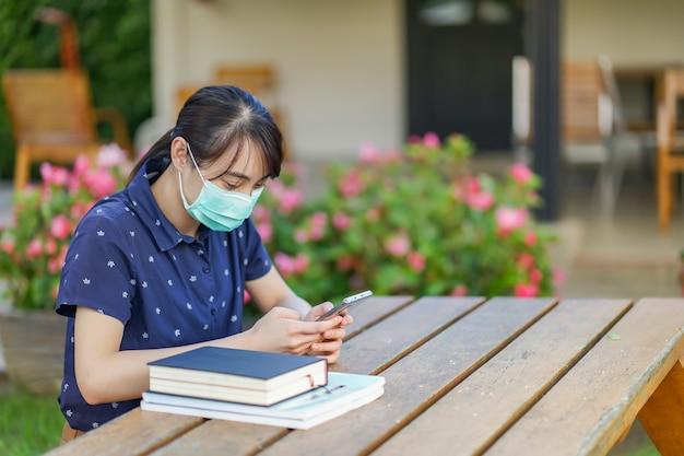 Giovane donna asiatica dello studente che indossa maschera medica e che tiene smartphone, esaminando schermo, facendo uso dell'app o di messaggistica mentre sedendosi al banco del giardino con il libro. nuovo concetto normale dopo covid-19 Foto Premium